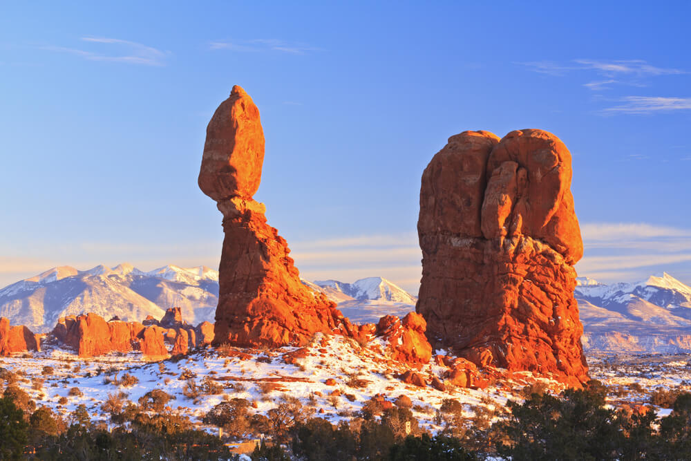 View of Arches National Park's famous Balanced Rock (a circular rock on top of a rock pillar) and another rock formation jutting out from the landscape, orange rock covered with a base of white snow.