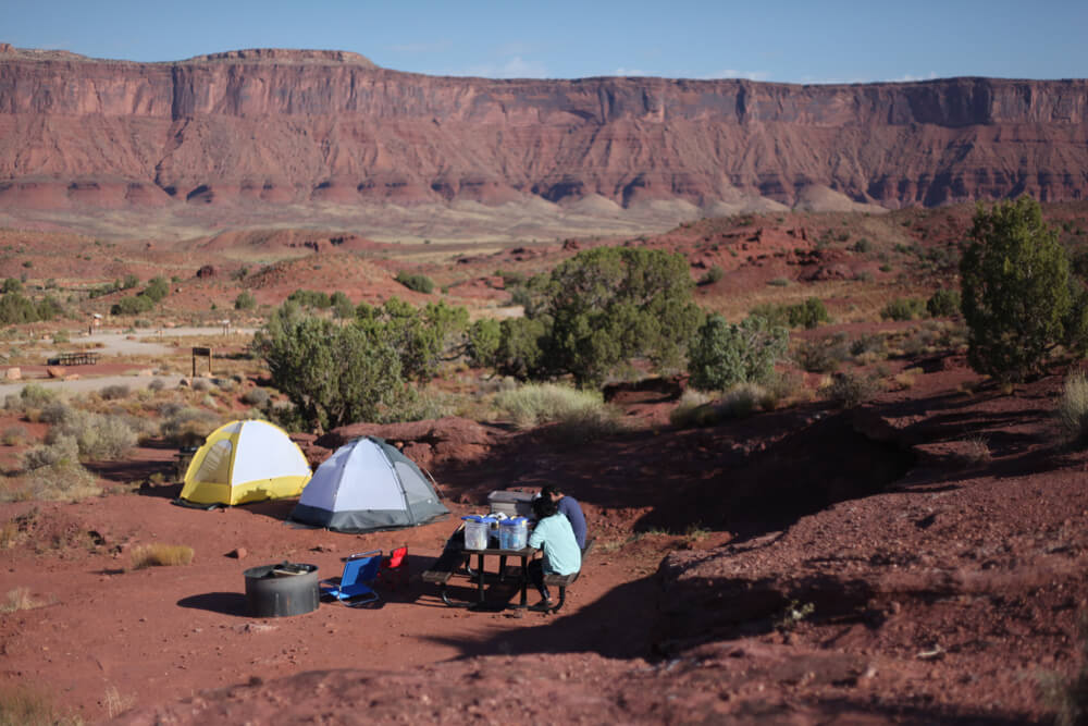 Two tents in a red rock Utah landscape near Arches National Park with people sitting at a picnic table.