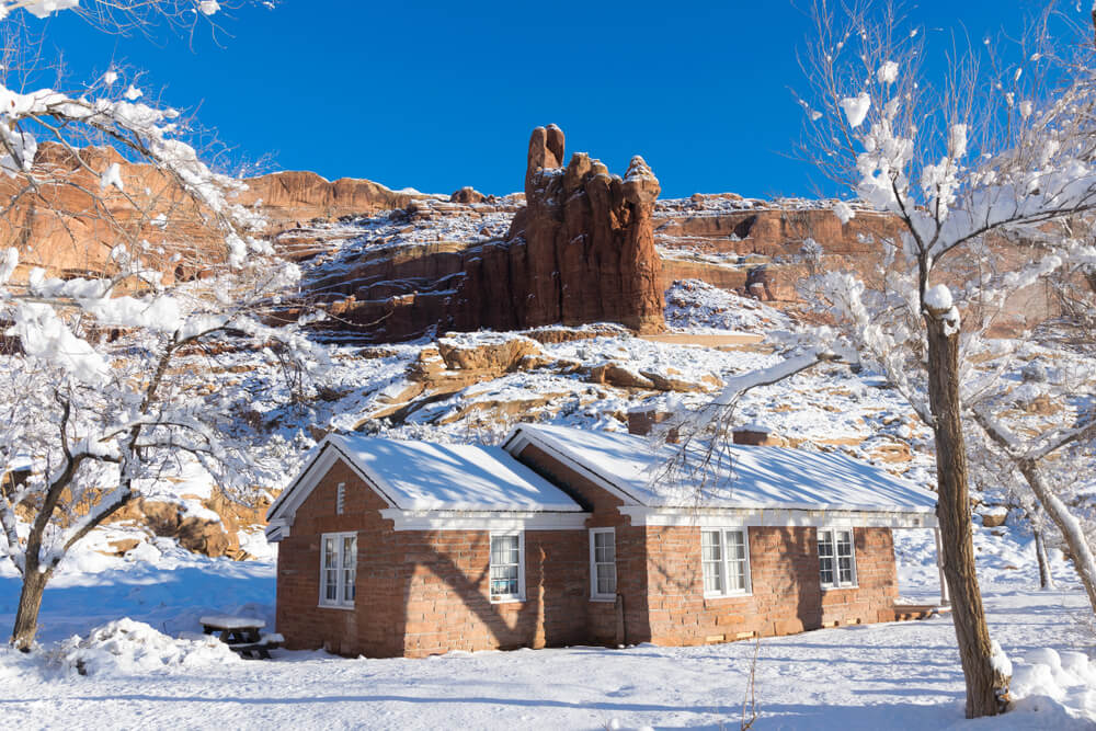 A small red brick building covered in snow surrounded by a red rock landscape with a light dusting of snowfall.