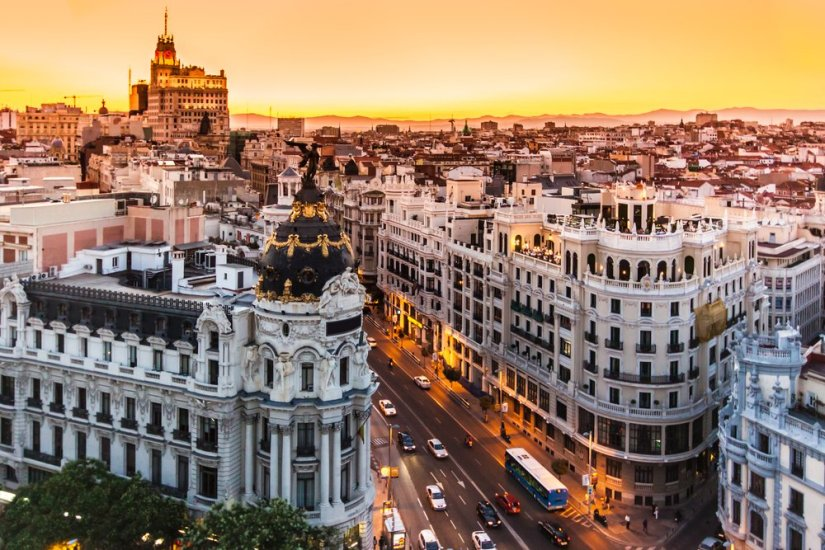 A view of a famous Madrid boulevard all lit up in pink and orange with sunset colors.