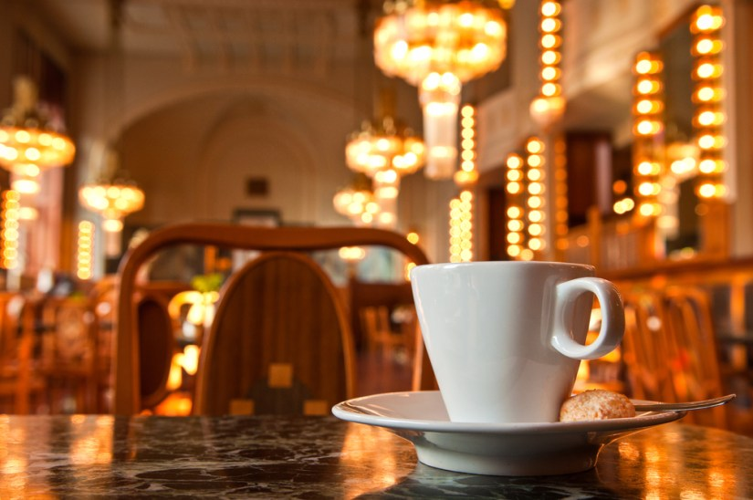 Cup of coffee in a cafe with lit up chandeliers and other lighting in background.