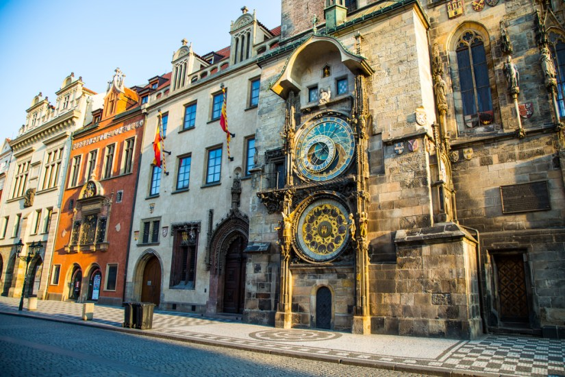 Astronomical clock in Prague surrounded by other old buildings with afternoon light shining on it.