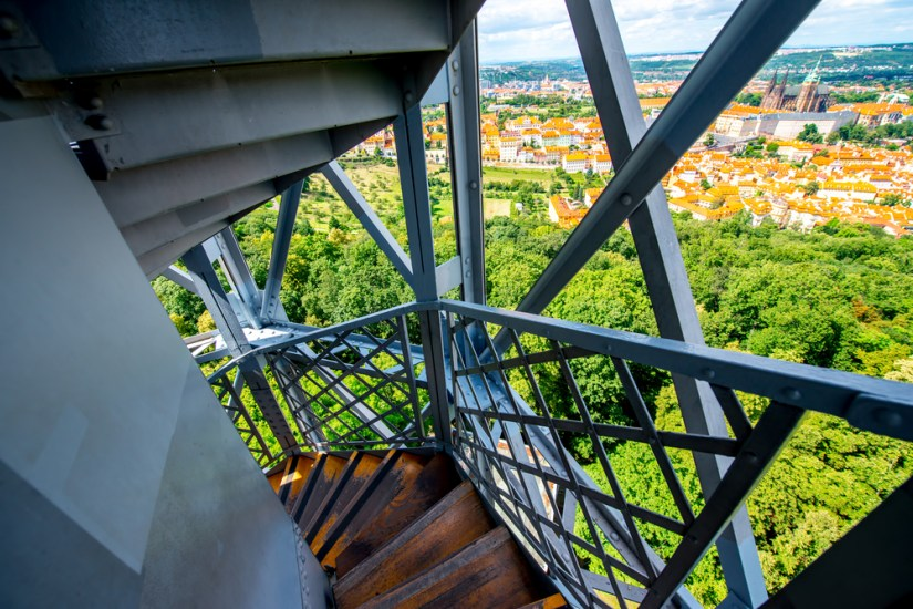 View of Prague park and distinctive red tiled roofs from the double-helix staircase of Petrin Tower, between the steel geometrical bars.