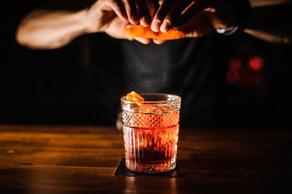 A man's hands making a cocktail, which looks to be a whiskey old fashioned, with an orange peel garnish, in a dark bar.
