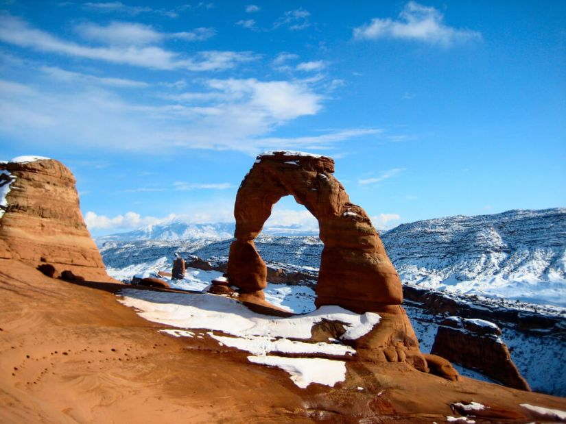 A view of a single orange sandstone arch against a backdrop of snow-covered mountains and a blue sky.