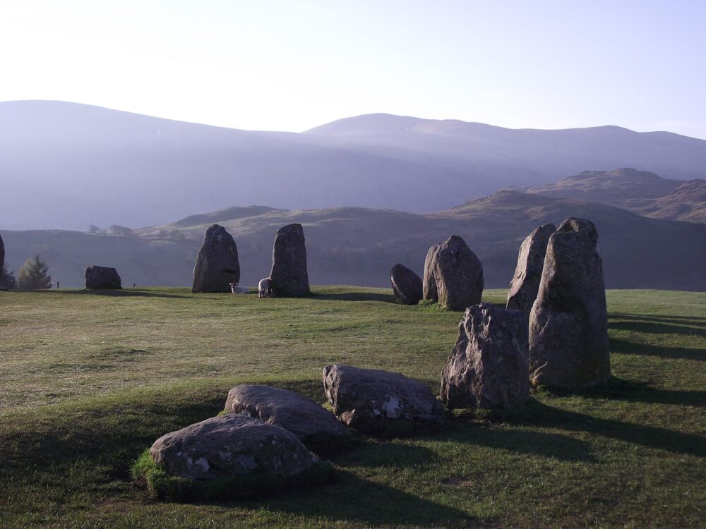 A circle of large stones casting a shadow in the late afternoon sunlight on Castlerigg in the Lake District.