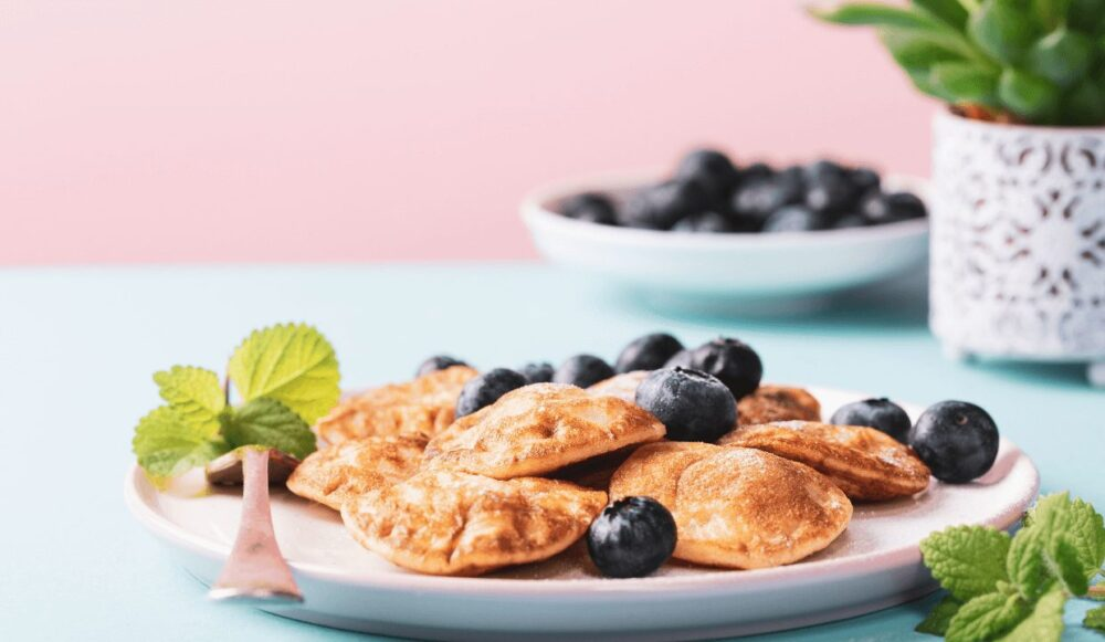 Traditional dutch pancakes served with blueberries and mint leaves.
