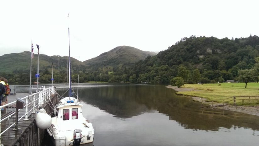 A jetty point where you can disembark from the steamboat, with a white smaller boat visible, and some hills on the lake in the distance.