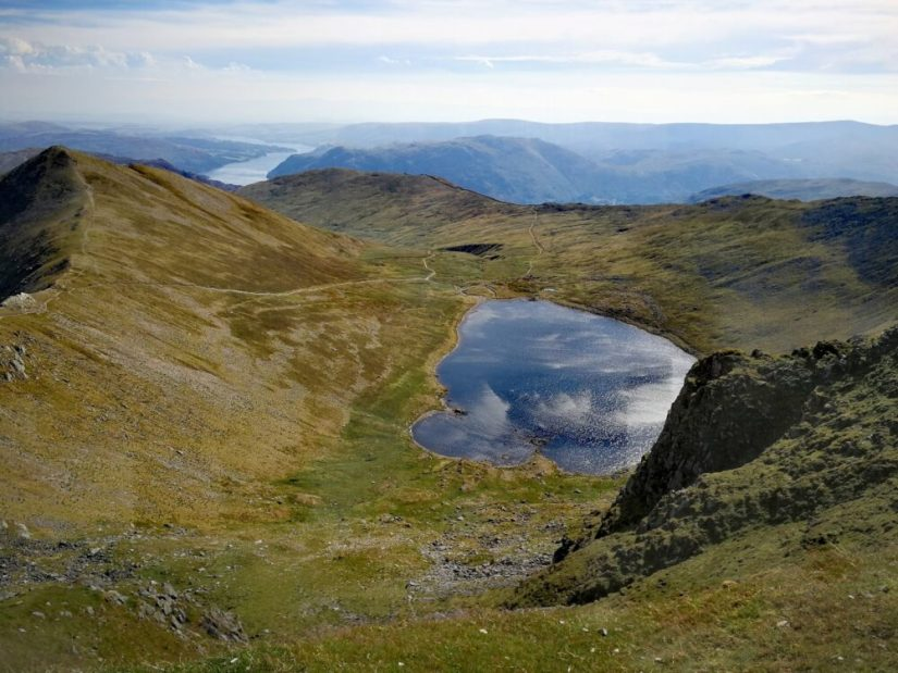 Helvellyn summit looking down to Red Tarn in the Lake District