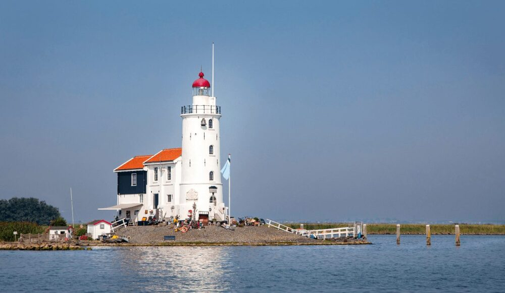A white lighthouse with an orange roof and black room at the back of the lighthouse, shown on the water, a true hidden gem in Amsterdam.