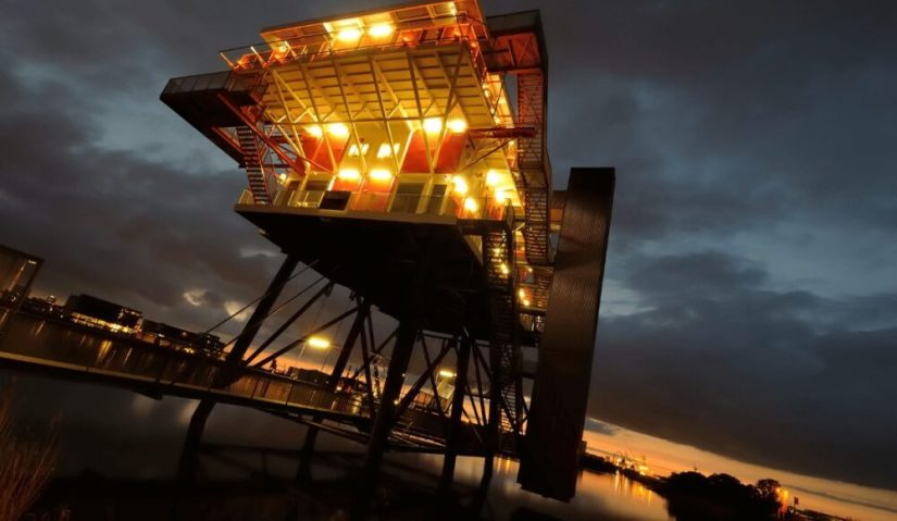 Lit up building on the water where you can dine in Amsterdam, a secret spot!