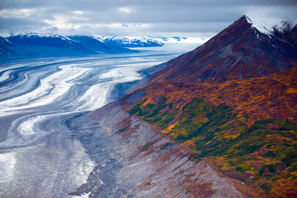 Ice fields in Canada surrounded by tall mountains covered in green and orange foliage and grass.