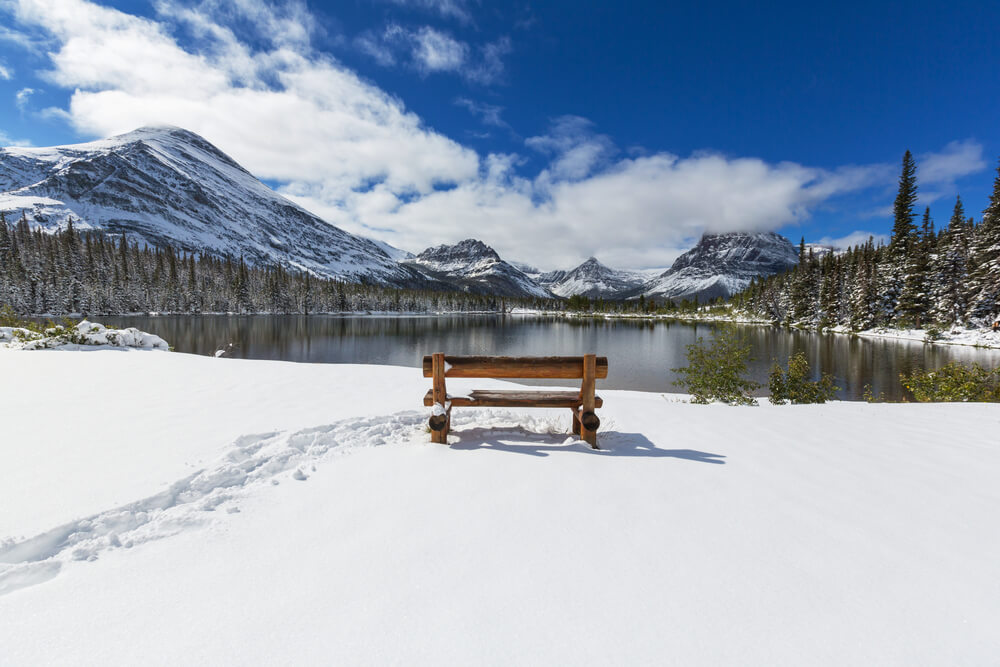 An empty bench with footstep tracks next to it, looking out over Lake McDonald and all the snow-covered mountains surrounding it.