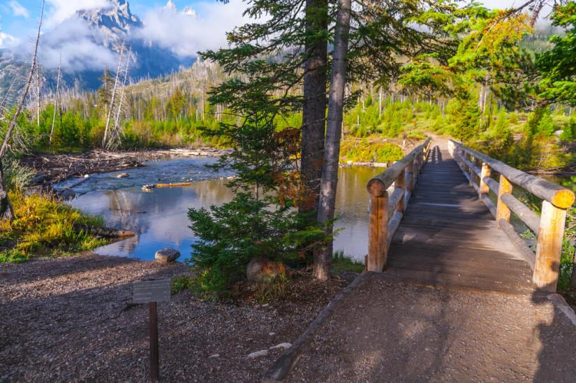 Narrow footbridge crossing a section of String Lake surrounded by green trees at the start of this Grand Teton hike.
