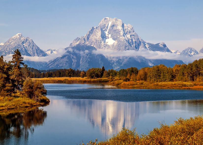 Mt. Moran at Oxbow Bend in Grand Teton National Park, reflected in the river which is surrounded by orange foliage in the autumn.