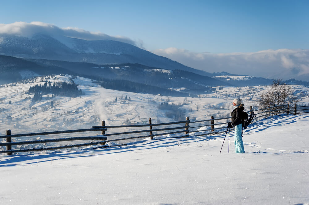 Female hiker in snowshoes with trekking poles wearing a black jacket and baby blue pants, looking over a snow-covered mountainous landscape in Glacier National park in the winter time.