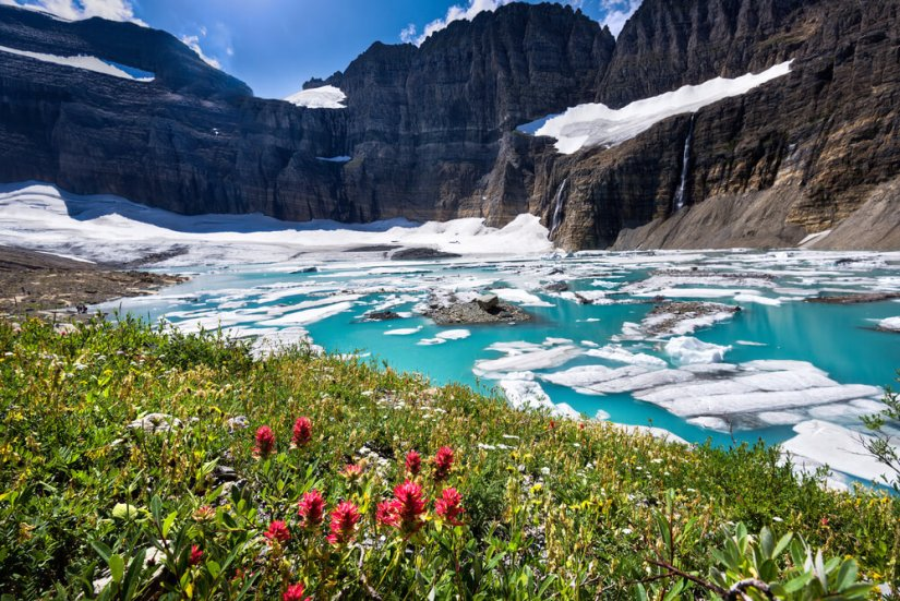 Brilliant turquoise blue water surrounded by white glacial ice, with green grass with red wildflowers on the edge, surrounded by tall mountain edges lightly covered in snow.