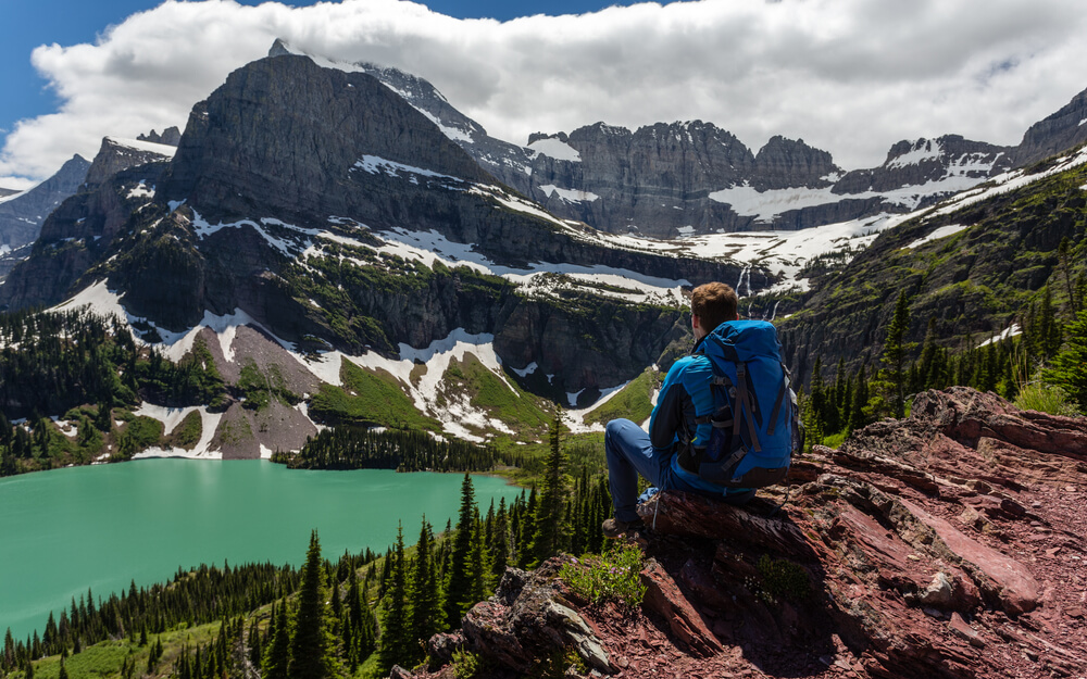 Male hiker wearing blue jacket and blue backpack sitting after doing some Glacier National Park hiking, looking over the teal colored Grinnell Lake, surrounded by mountains dusted with some remaining snow.