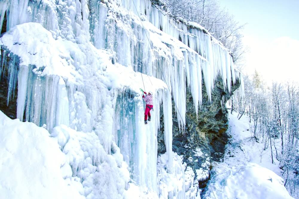 A woman in a pink jacket and red pants climbing up the icicles of a frozen waterfall with climbing equipment and harness.