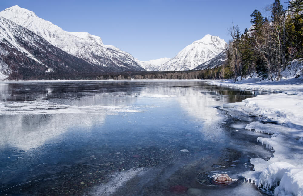Icy surface of Lake McDonald as seen in winter, wth snow and ice on the banks of the lake, with snow-covered mountains in the distance.