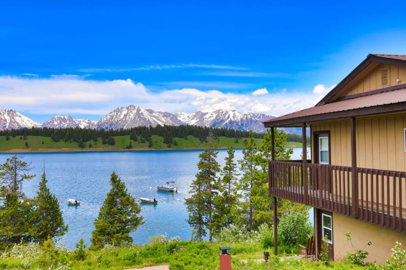 A two-story cabin overlooking a lake in Grand Teton National Park, surrounded by mountains and trees, with a few boats out on the lake on a sunny day.
