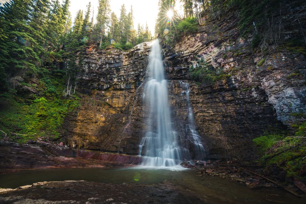 Waterfall cascading over a cliff, with trees surrounded the edges of the cliff with a small sunburst poking through the trees.