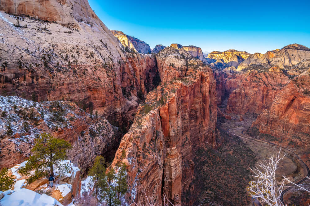 View of Zion's red rock cliff landscape juxtaposed with bits of white snow in the higher elevation crevices of the canyon on a blue sky winter day in Zion National Park