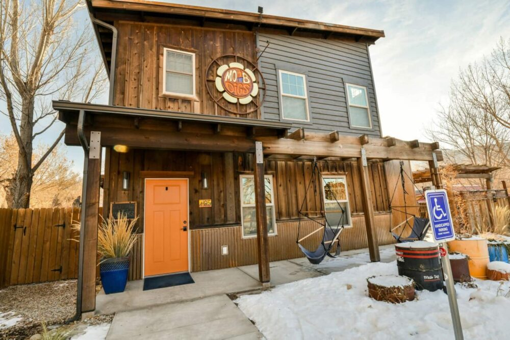 """Wooden two-story house with orange door and two porch swings in front with a sign on the Moab airbnb which reads """"Moab Digs"""""""