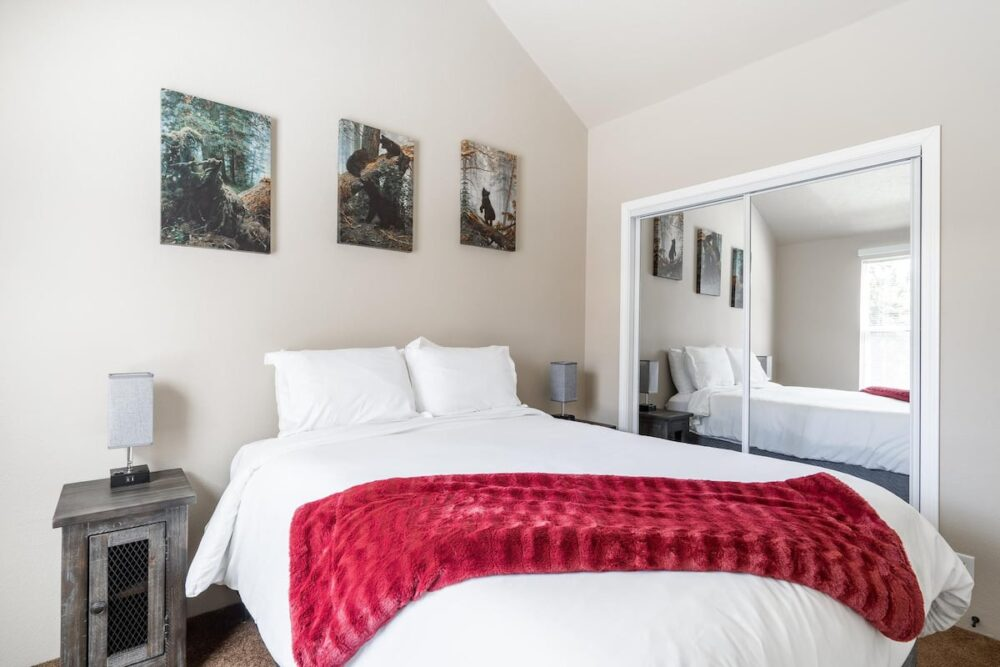 A white bed with a red blanket with 3 photos above the bed.