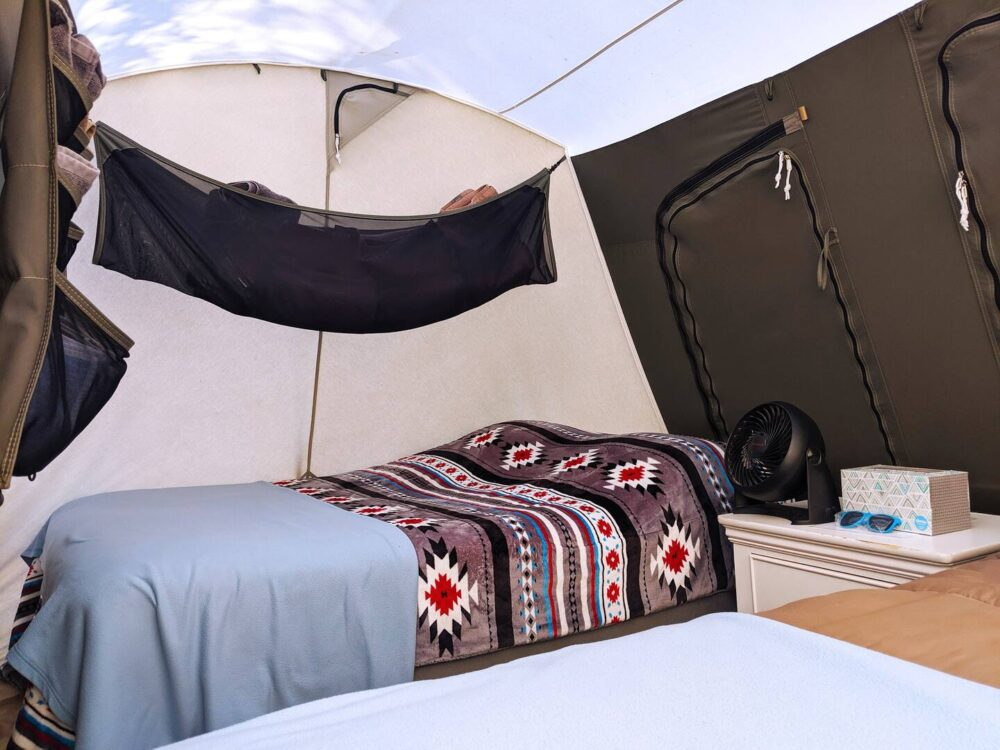 Large canvas glamping tent with two queen size cots inside with storage places.