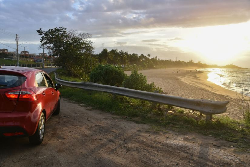 a red car at sunset on a beach in puerto rico