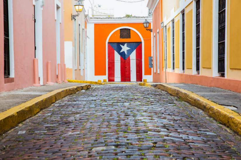 a mural of the puerto rican flag surrounded by colorful walls and cobblestones