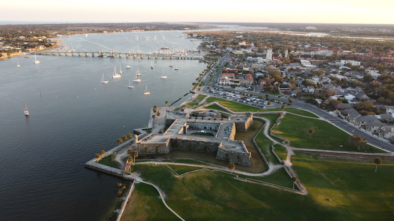 A drone photo of of a fort shown in the shape of a star, with the view of water and a bridge and sailboats in St Augustine FL