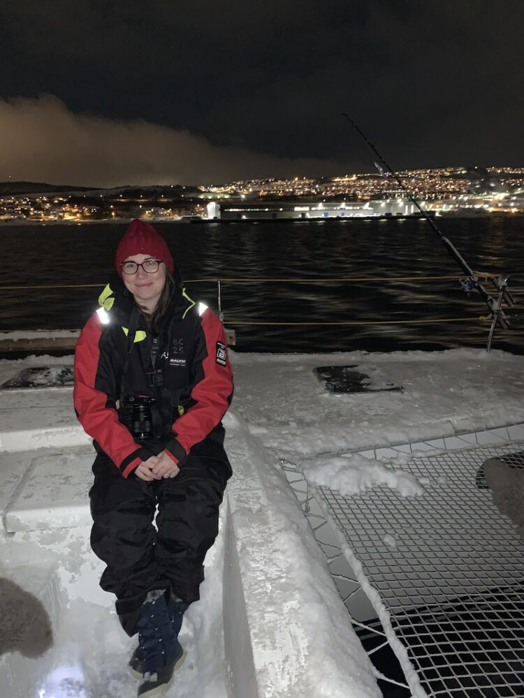 Allison sitting on a snow-covered catamaran sailing in the Norwegian fjords
