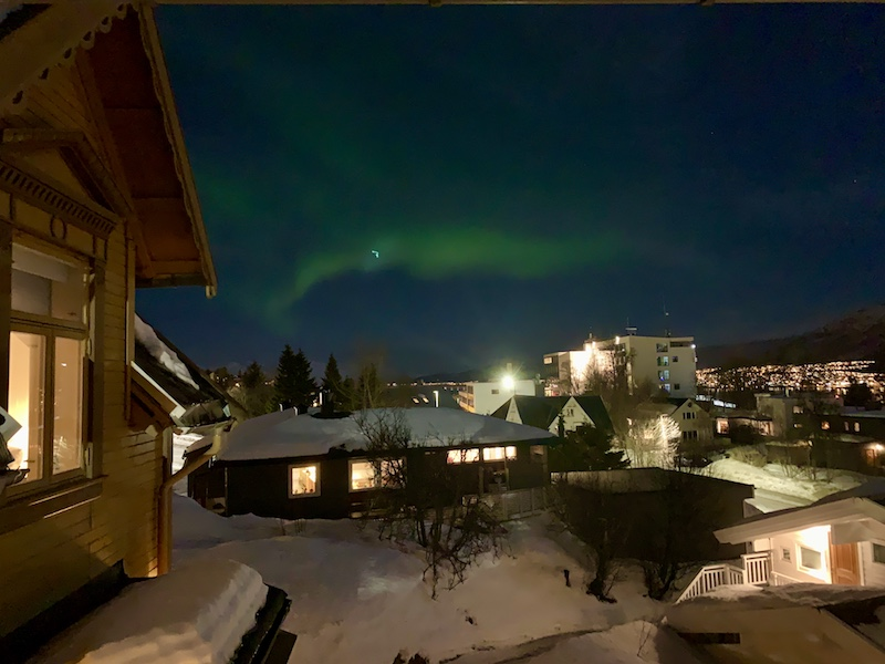 faint northern lights occuring in the city center of tromso