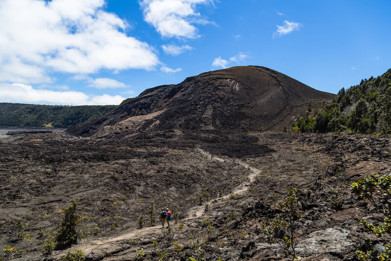 people hiking on the Kīlauea crater trail with volcanic landscapes on a sunny day