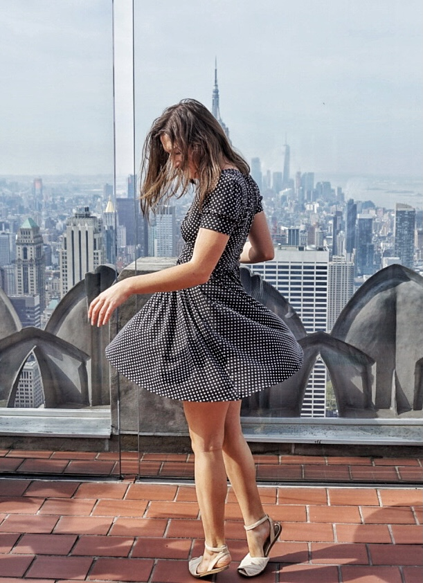 Allison Green spinning in a polka dot dress in front of the Empire State Building at the Top of the Rock