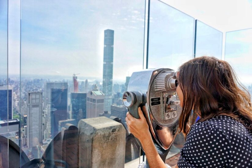 Allison Green smiling as she looks through a viewfinder at buildings in NYC