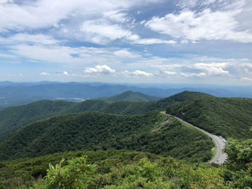 view over a hiking trails, lots of green trees and a highway cutting through the mountain