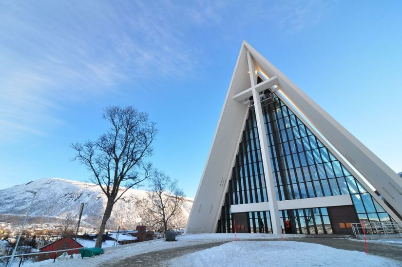 Large white church with a big cross and snow and views of mountains in distance on a sunny winter day. Arctic Cathedral is a must on a Tromso itinerary