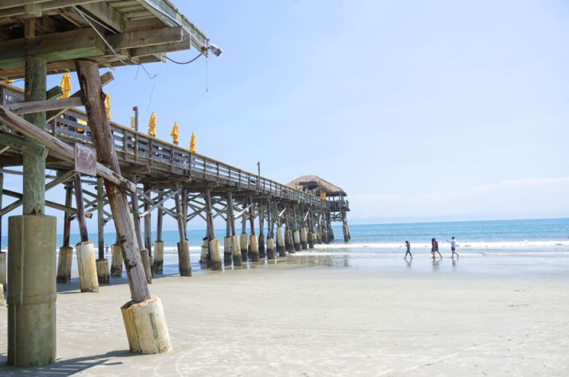 pier in cocoa beach florida with three people walking on the beach sand