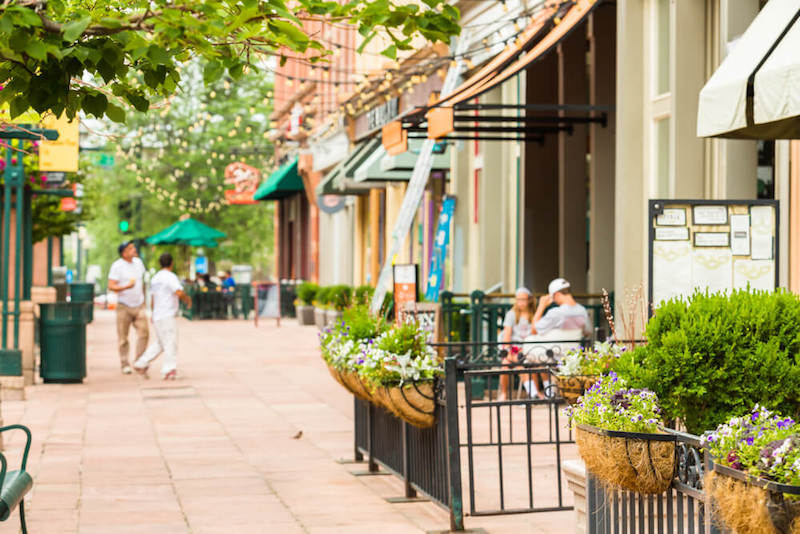 The historic downtown area of Denver with summer plants and people out enjoying restaurant seating outdoors