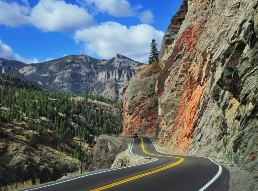 Road against the edge of a mountain with lots of evergreen trees in the distance on a sunny day road tripping Colorado