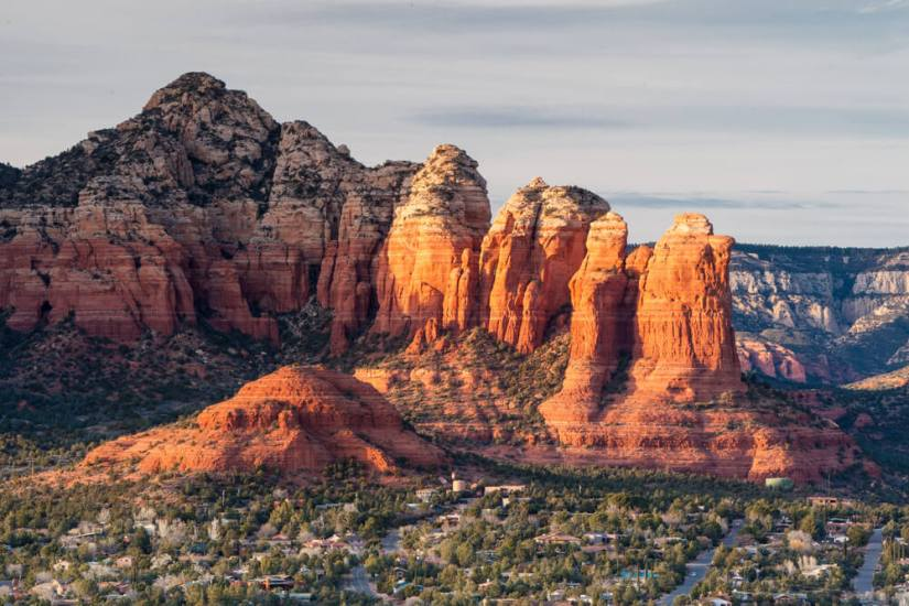 Falling light of the sunrise or sunset casting a glow on the red rocks of Sedona overlooking the Verde Valley with green trees in the valley