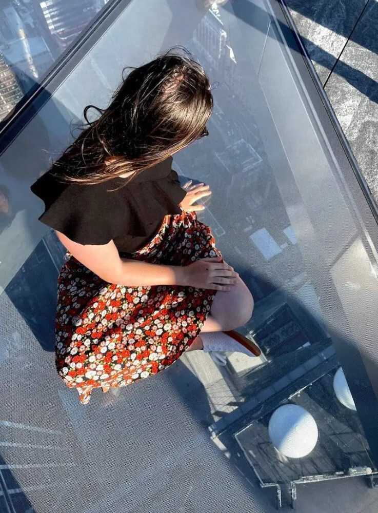 Allison Green looking below on the glass floor of the sky deck at The Edge observation deck in NYC, wearing a black shirt and red floral skirt