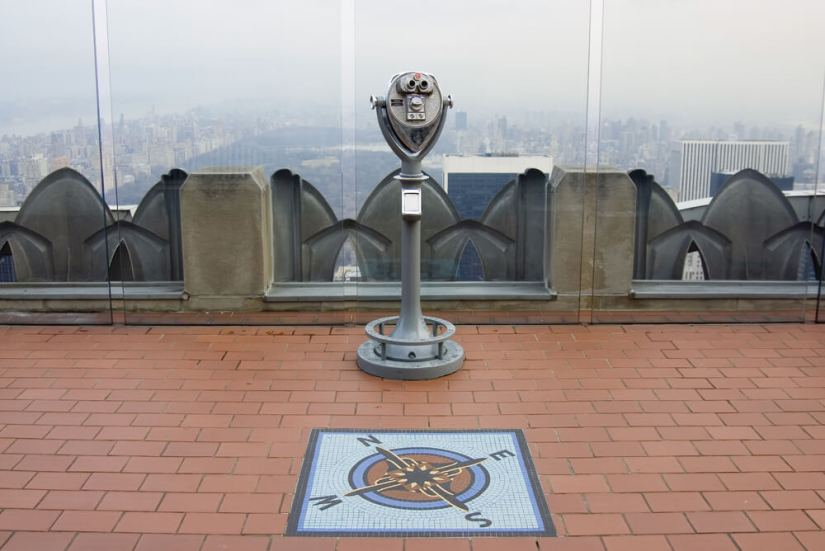 Vintage viewfinder with Central Park in the distance and a compass mosaic on the ground