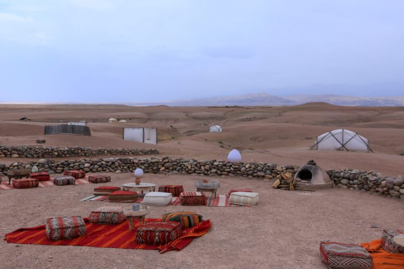 Cushions set up around tables to enjoy tea in the rock desert outside of Marrakech
