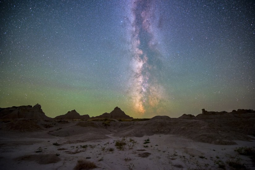 The colors of the Milky Way stretching up over the horizon in Badlands National Park, South Dakota