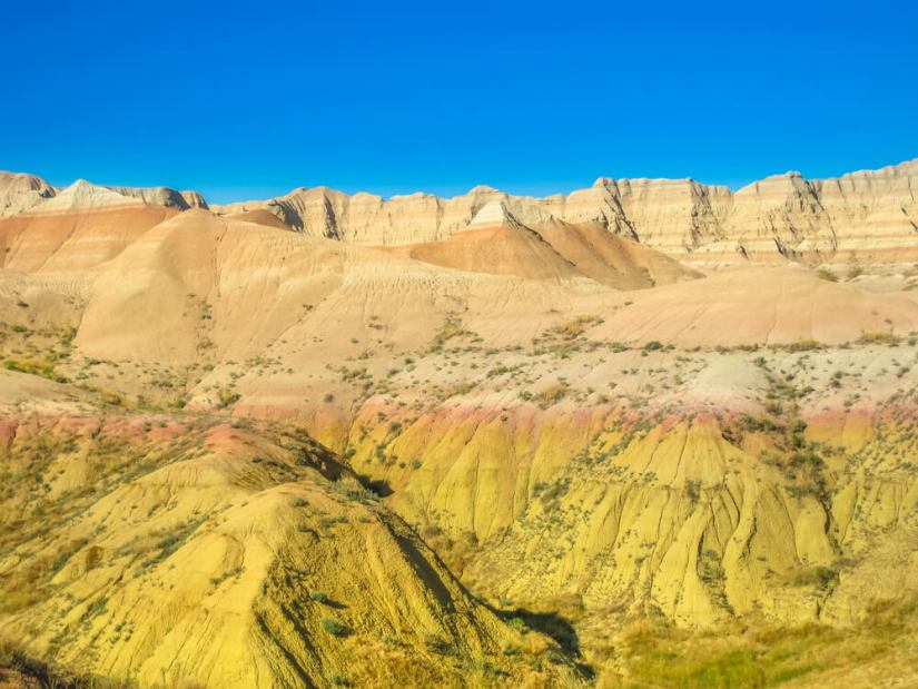 Yellow mounds in Badlands National Park with stripes of orange, tan, and pinkish-red with a clear blue sky behind it