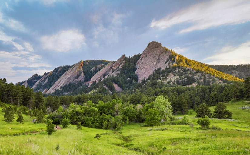 The distinctive rock formations of the Flatirons which look like three irons in a row surrounded by trees